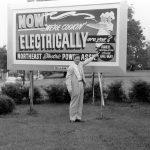 A man pointing to a sign. Now We're cookin' Electrically are you? Northeast Electric Power Assn. Free Installation during Apr. and May