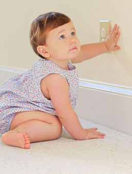 An infant touching the wall near an electrical outlet.