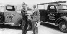 Black and white photo of a man from Riverside Dairy Grade A Milk, and a man from NEMEPA shaking hands next to their trucks.